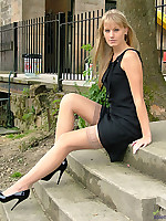 Blonde outdoors in lacy stockings and patent heels