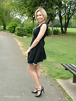 Hot Milf Monica posing in a gorgeous short black dress with matching shiny bumptious heels